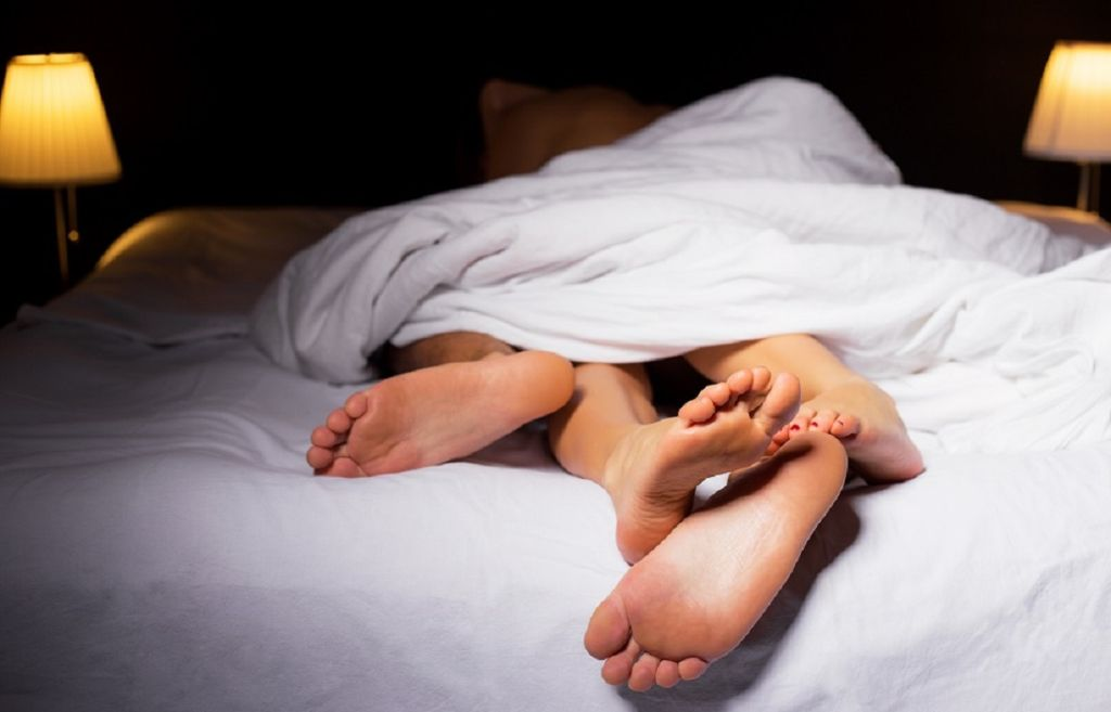 couple sleeping in bed under a white sheet, only their feet visible