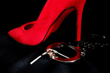 An image with a red heeled shoe and a silver handcuff on a black background