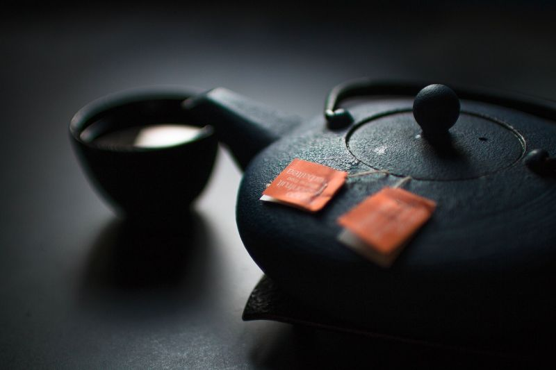 A black teapot and tea cup