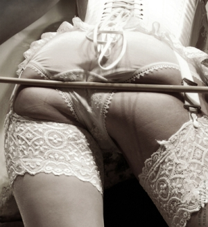 A woman's bottom with a cane pressed against it.