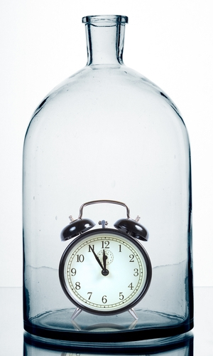 An image of an alarm clock in a glass bottle.