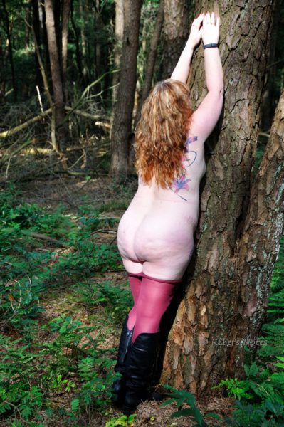 Half-naked and leaning against a tree.