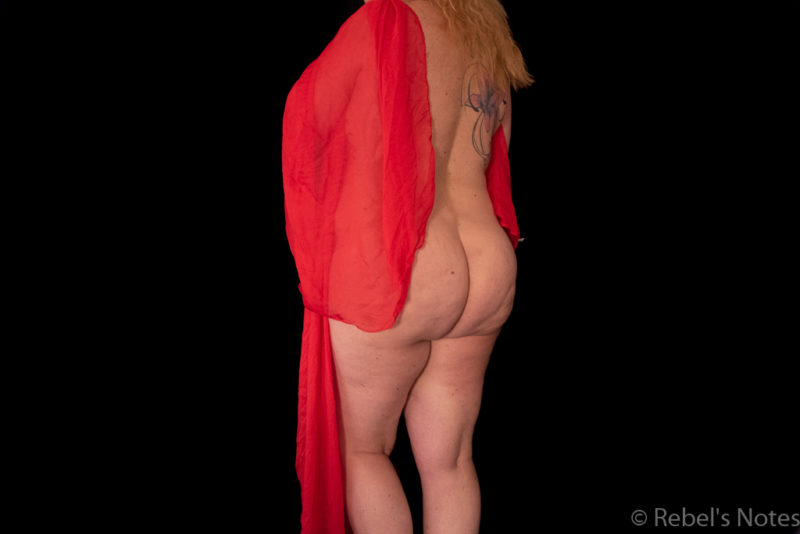 An image of Rebel holding a red scarf, her naked back, bottom and legs visible.