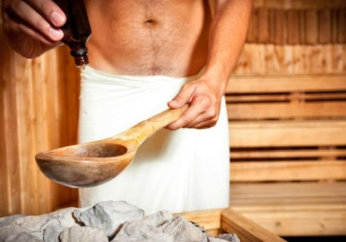 A man with cloth around his loins getting ready for a sauna infusion.