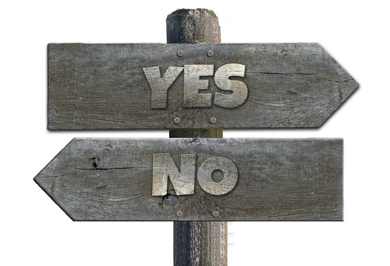 An image showing two wooden signs, one pointing left, the other right, saying 'yes' and 'no'.