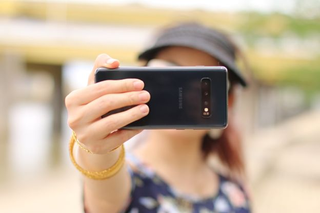 An image of a woman taking a selfie of herself, her face obscured by the phone.