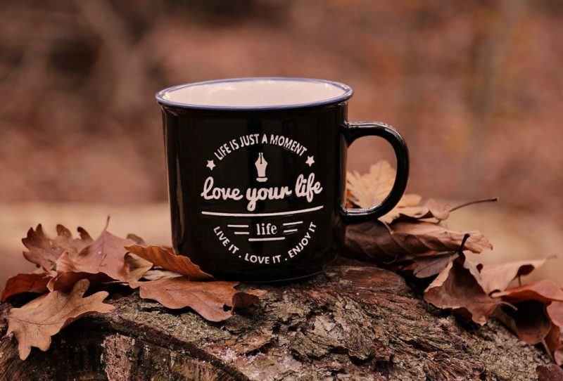 An image of a black cup with white printing saying 'love your life' to go with my post 'Life happens, love binds'.