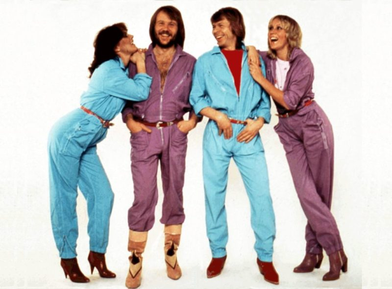 An image of ABBA dressed in overalls, two in light blue, the other two in purple.