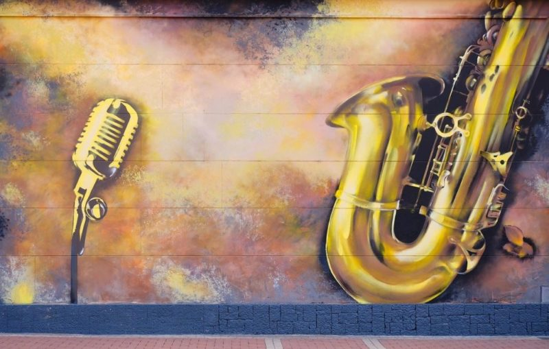 A wall painting with a saxophone and an old-fashioned microphone frequently seen at jazz performances.