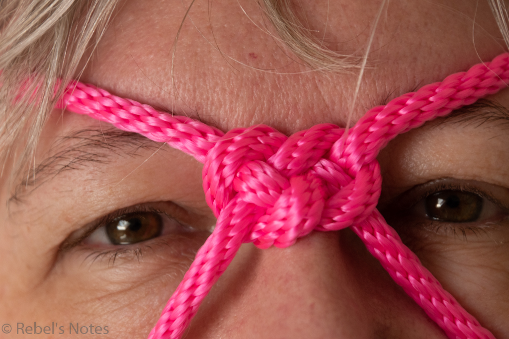 A close-up image of the pink knot in the rope, resting between my eyes, and of course my eyes are visible too.
