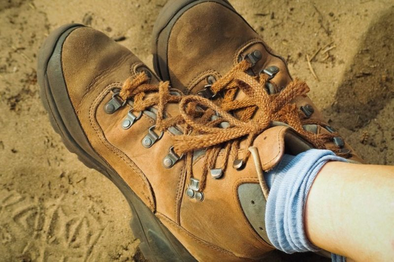 An image of light brown hiking shoes and light blue socks, resting in the sand, legs crossed.