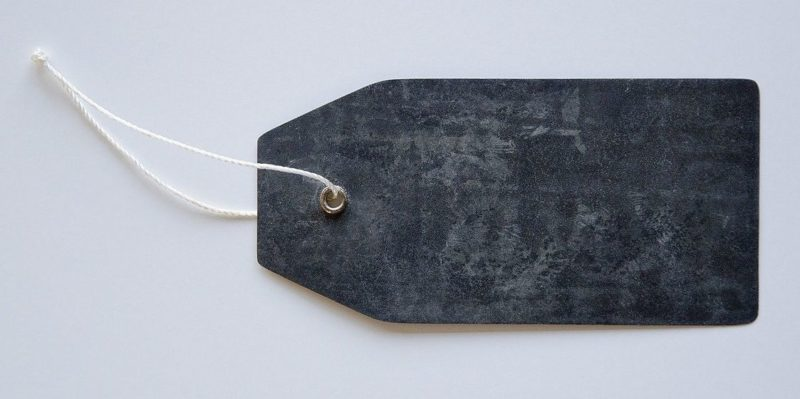 An image of a dark grey tag with a white string attached to it, seen on a light grey background.