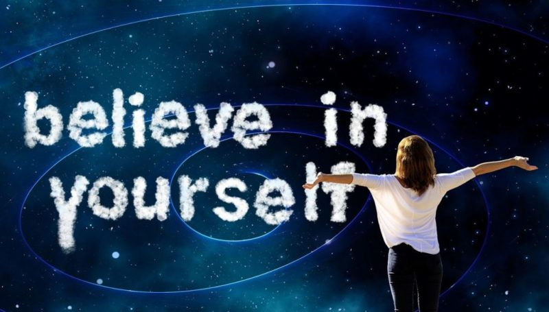 An image with the words 'believe in yourself' and a woman with her arms stretched out looking at those words