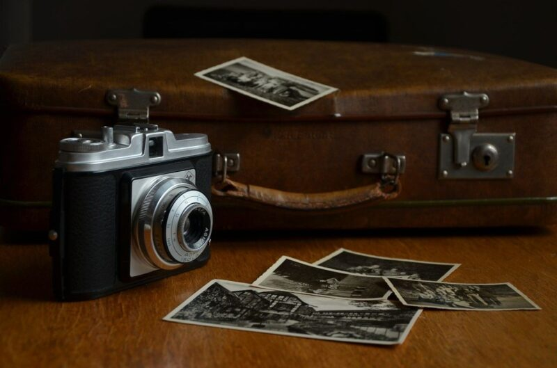 An image showing an old camera and suitcase, and some old photos, implicating memories from the past.