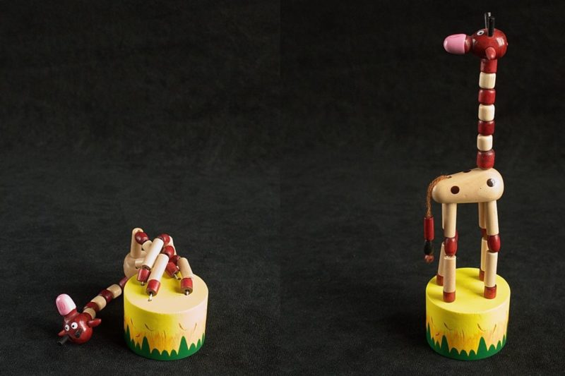 An image showing a giraffe push puppet, one part collapsed, the other part upright.