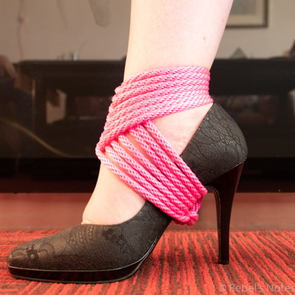 An image of my foot with a black heel show and a pink rope around it forming a heel tie.