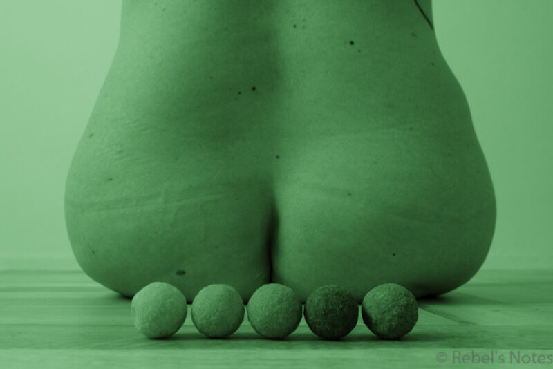 An image of my bottom, with five chocolate truffles in the foreground. The image is in monochrome green.