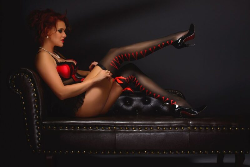 An image showing a woman dressed in a red and black corset, and putting on red and black stockings, with black shoes - a perfect kink image for those with a shoe or nylon fetish.
