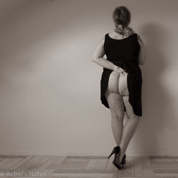 Me in a black dress, lifting it at the back to show my bottom. Monochrome image.