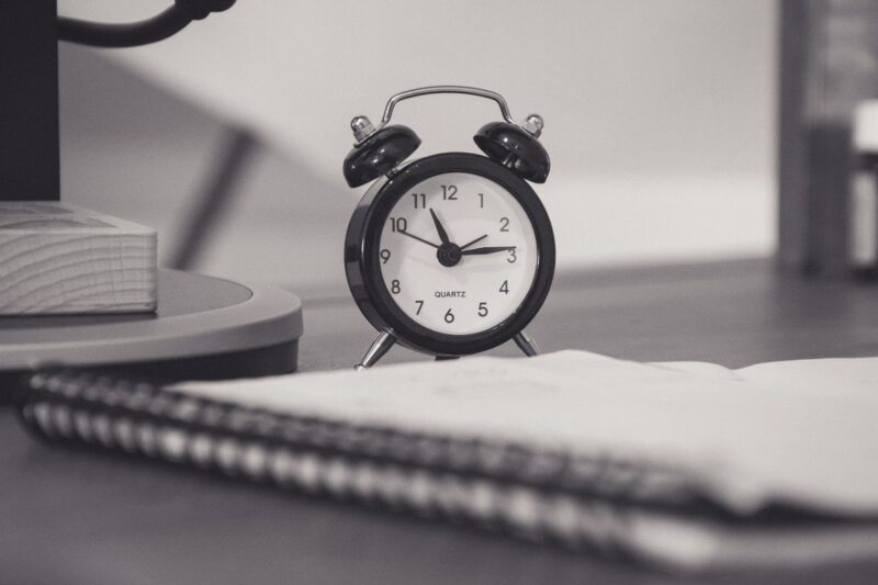 Black and white image with a book and a clock, imitating setting your priorities and managing your time.
