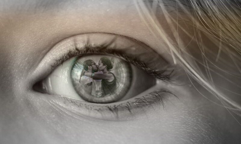 An image of an eye, and inside the eye is two people kissing. This image is the expression of desire.