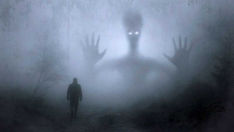 An image of a man walking in the woods, with a ghost holding up its hands in the mist, portraying being haunted.