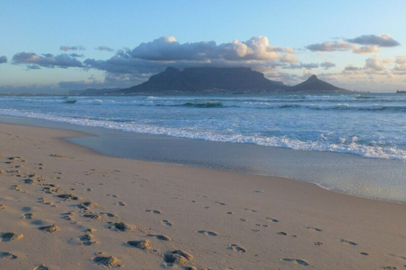 A photo of Table Mountain, South Africa, seen from Bloubergstrand and showing footprints in the sand.