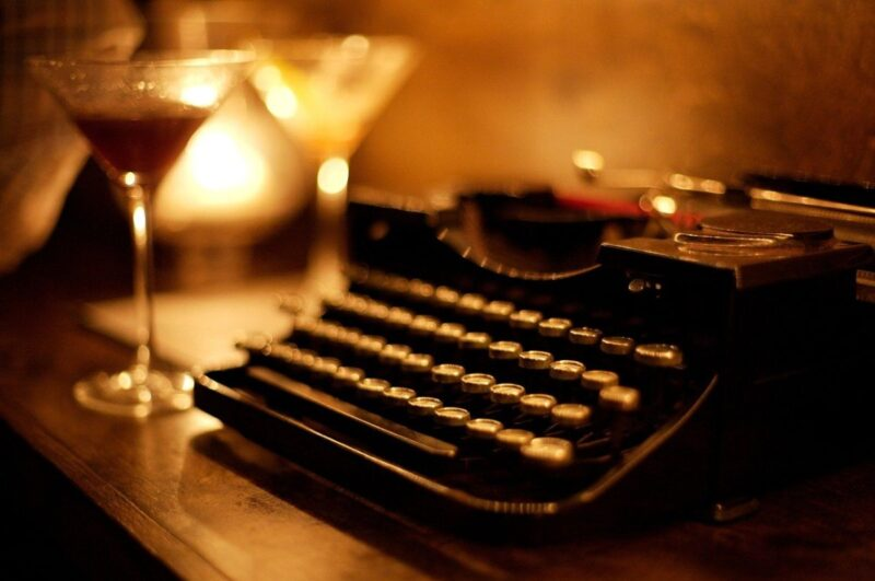 An image of a typewriter and a cocktail glass, perfect for this post about NaNoWriMo 2020.
