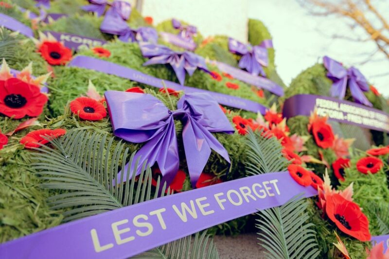 An image showing red poppies for Remembrance Day, and the words Lest we forget on a purple banner.