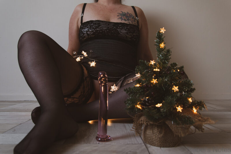 An image of me in the background, a tiny Christmas in front of me, as well as a glass dildo.