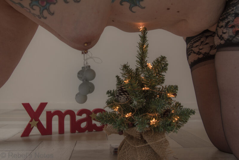 An image of me, showing my breasts with Christmas baubles hanging from it.