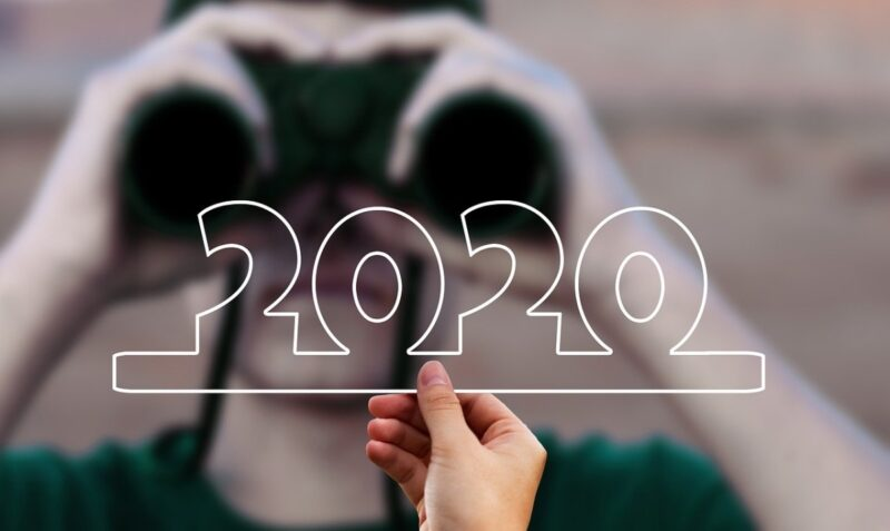 An image of a hand holding the numbers 2020, and binoculars in the background for looking back on the year.