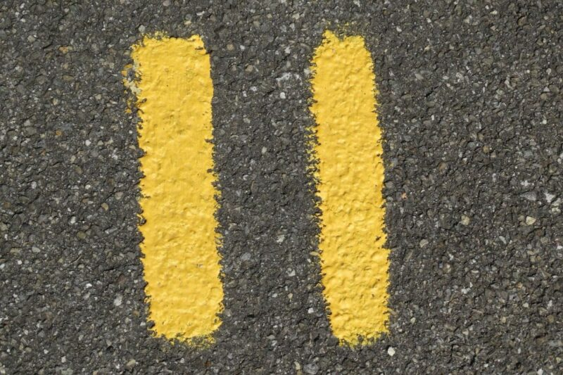 An image of a street with the number eleven painted in yellow.