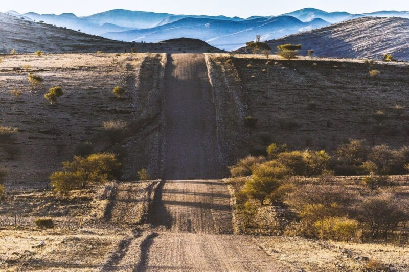 A straight gravel road over the hills in Namibia, perfect for cruising with the music