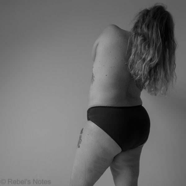 An image of me, leaning away from the camera, wearing only knickers, and when I look at it, I see a beautiful girl.