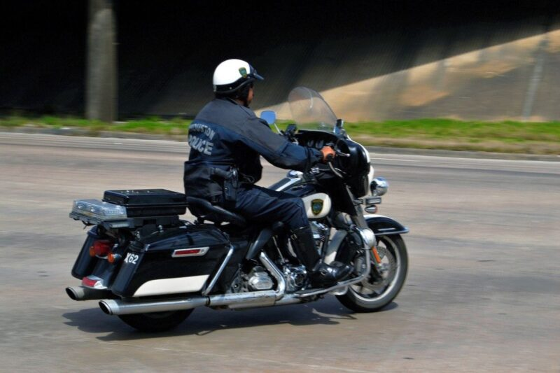 An image showing a police officer on a motorcycle.
