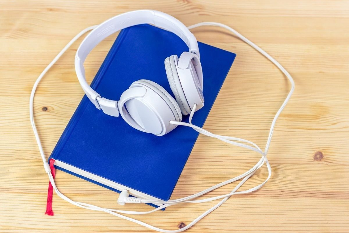 An image of a blue book and white headphones, to indicate reading a book by listening to it.