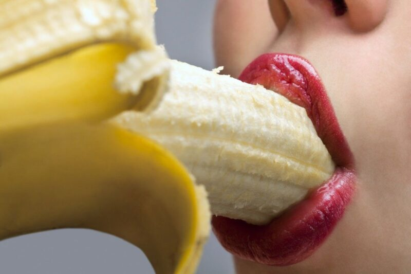 An image showing a mouth with red lips and a banana in it, mimicking oral sex