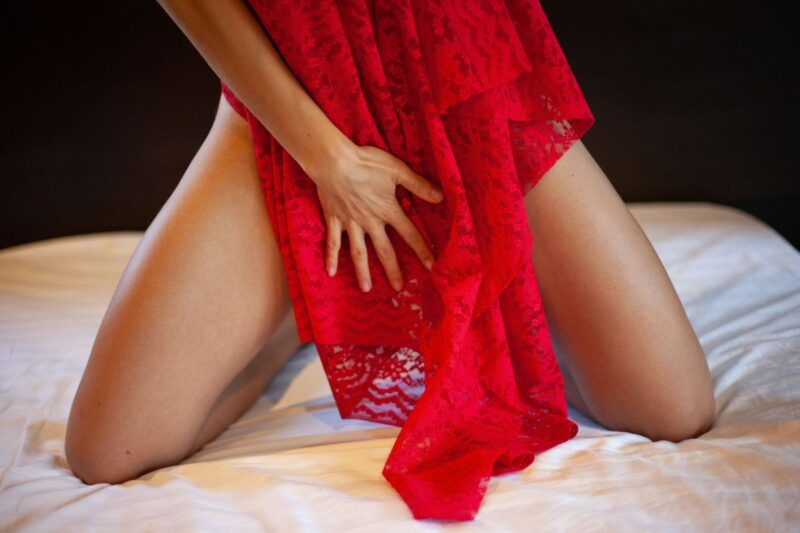 An image of a woman on her knees, holding a red lace garment in front of her, to go with this story about a greedy little slut.