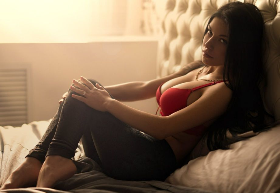 An image of a dark-haired woman wearing a red bra and brown pants, sitting on a bed, looking into the camera to go with the article called Everything You've Ever Wanted to Know About Escorts.