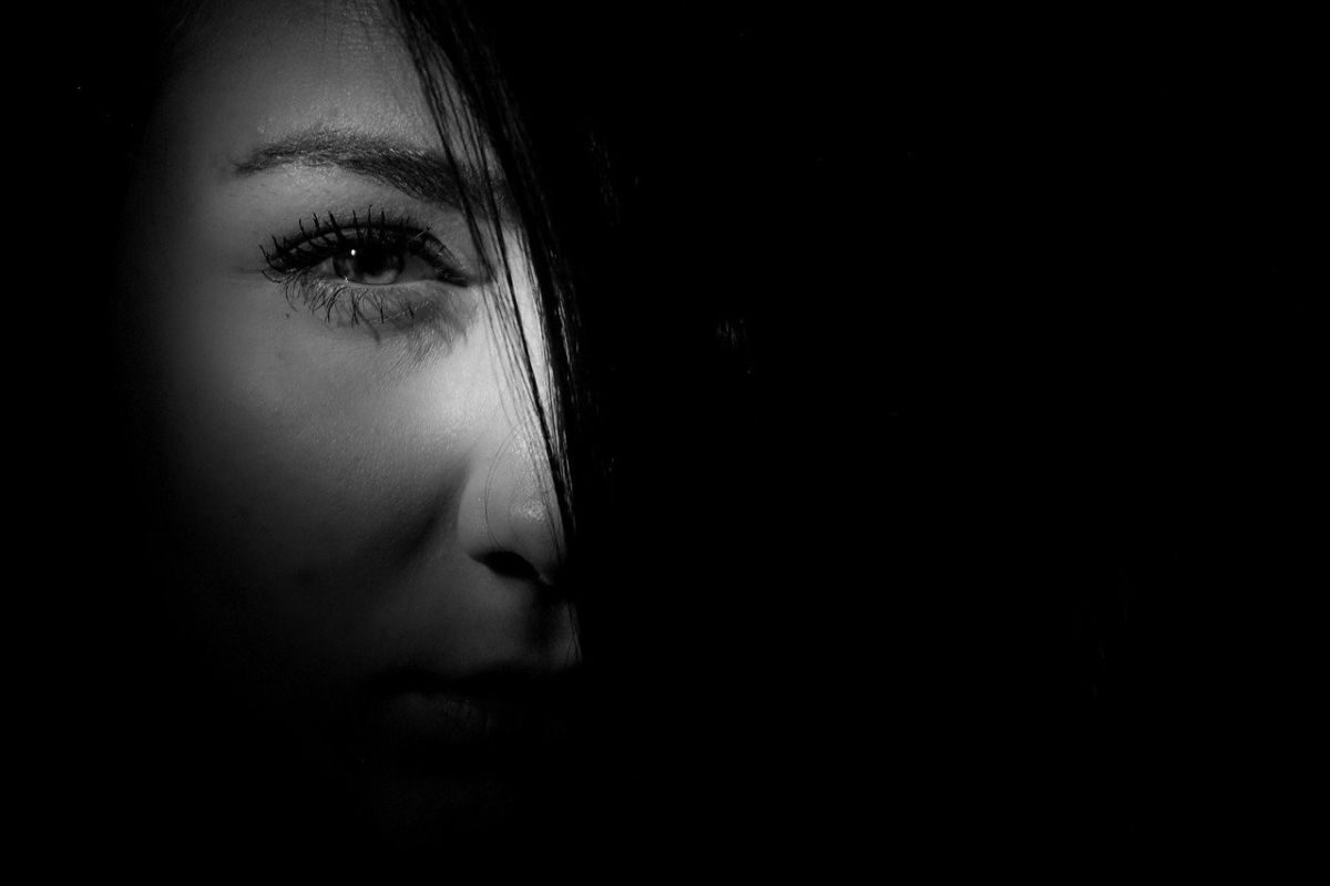 An entirely black image with only part of the face of a woman seen though a hole to go with the story about glory holes.