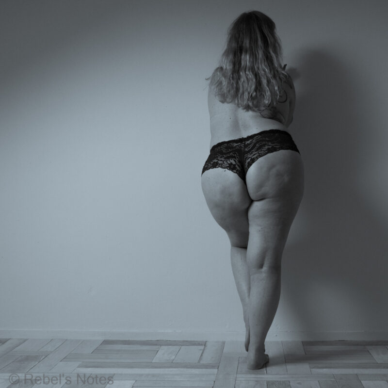 An image of me leaning against a wall, my bottom pushed back. I am wearing only panties, and this image goes well with the Sara Blakely quote to make the world a better place, one butt at a time.