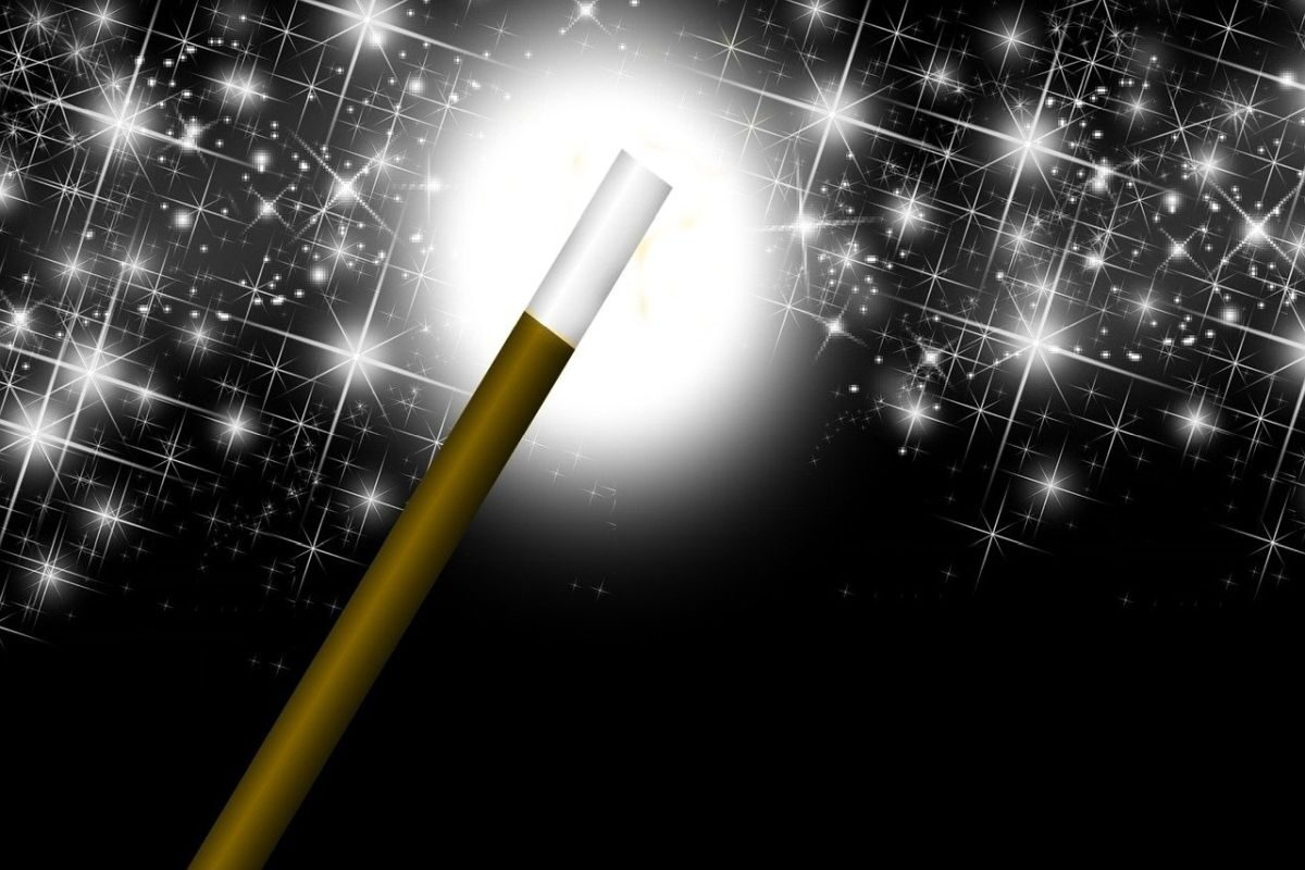 An image of a magic wand and white stars on a black background, to go with my post about tricks of the trade.