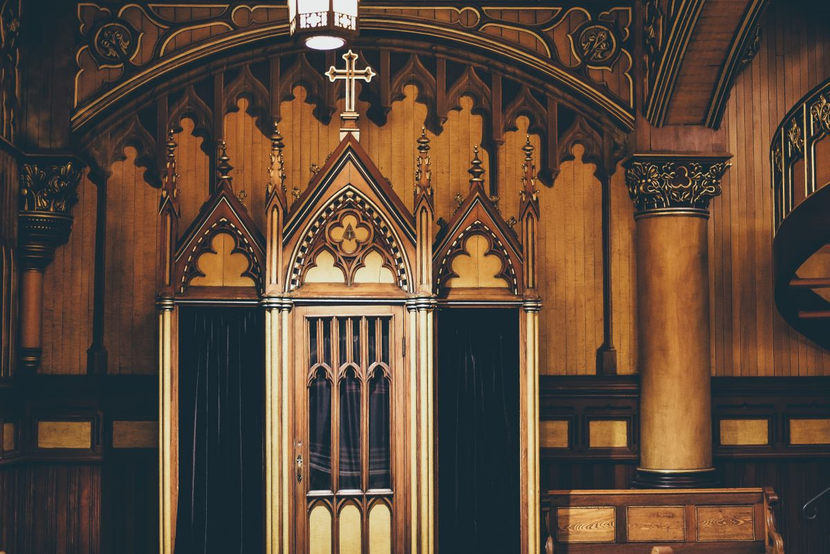 Image of a confession booth with a heavy black curtain, to go with my story about Hope and her shenanigans in the confession booth.