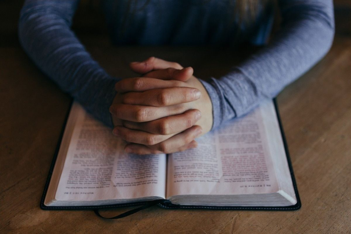 Image of a man folding his hands in prayer, resting on a Bible, to go with my naughty story about Charity being in the chambers of the priest.