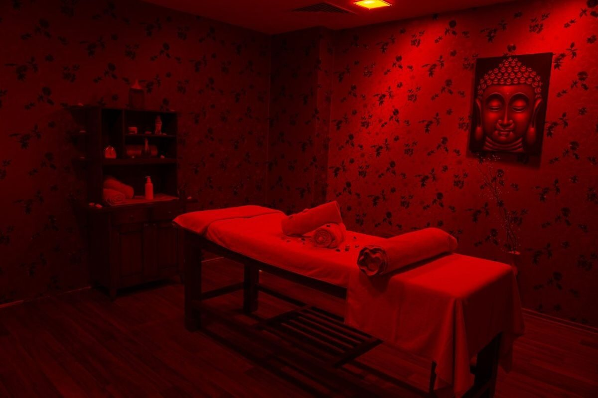 A darker image in red tones of a massage table in a massage room, the perfect place for a tantric massage.