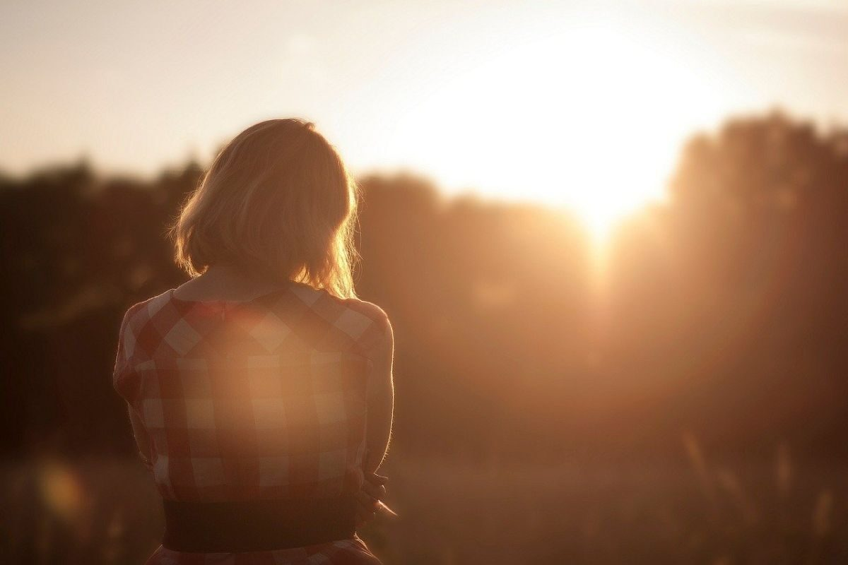 Image of a woman looking at the sunset, and seen from the back to go with my post 'I hate to be alone'.