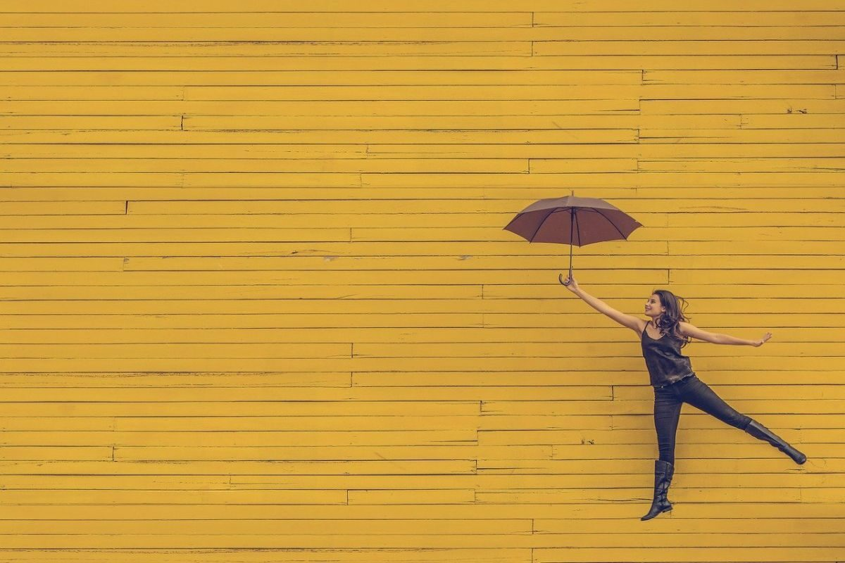 An image of a woman floating against a yellow background, holding an umbrella, to go with my post about superpower.