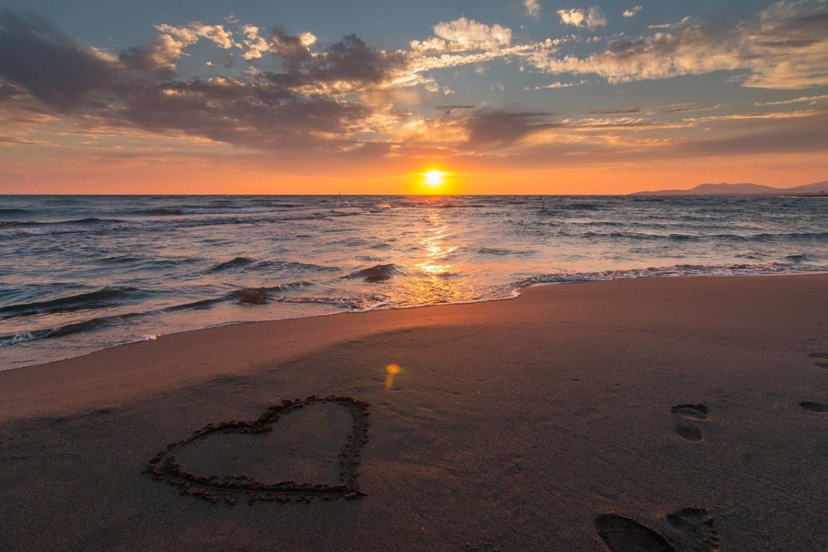 An image of the ocean, the beach, a setting sun and a heart drawn in the sand to go with my story 'Love is Love'.
